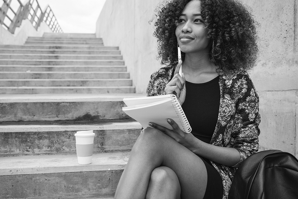 Portrait of young afro-american woman thinking while sitting outdoors on stairs with notebook and pen.